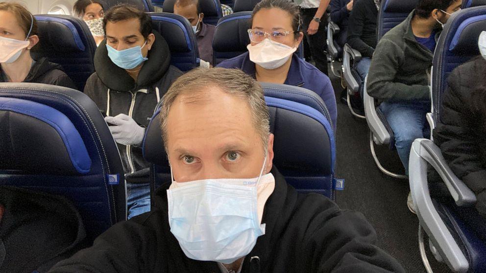 avión lleno de pasajeros con mascarillas