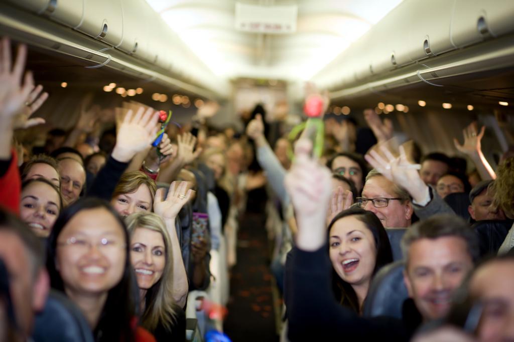 Noticias de aviación. Noticias de aviones. Pasajeros en la cabina de un avión divirtiéndose.